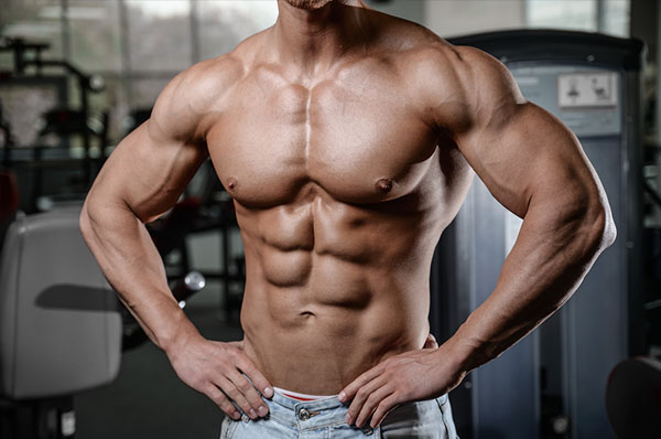 Strong and handsome athletic young man with muscles abs and biceps. Close-up of a power fitness man